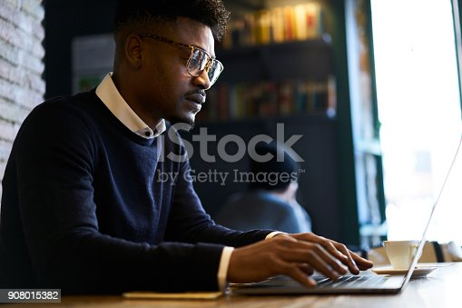 istock Skilled afro american copywriter creating text content for web advertising keyboarding on laptop computer connected to free wireless internet in coffee shop wifi zone working on free schedule 908015382