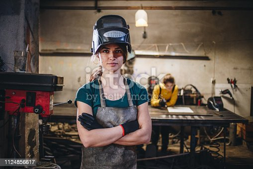Young sisters working in their workshop together, welding and cutting things out of metal.