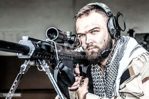 istock Skilled army sniper aiming with optical sight 1073085986