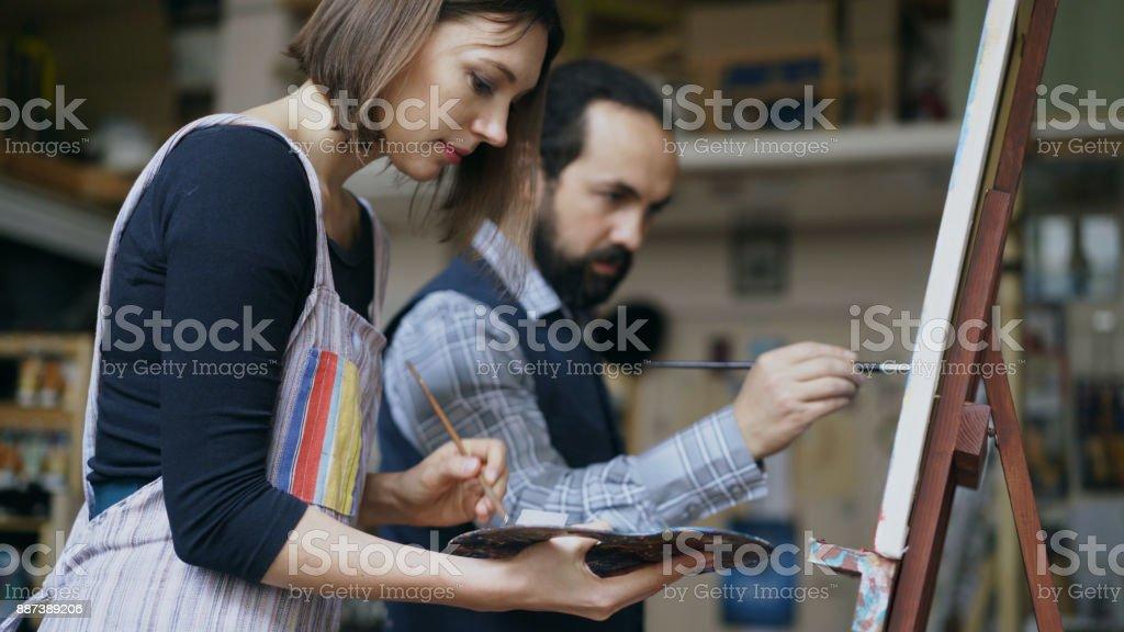 Artista experto hombre enseñanza joven pintura en caballete en el estudio de la escuela de arte - creatividad, educación y concepto de gente de arte - foto de stock