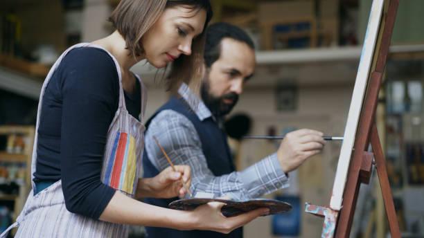 artista experto hombre enseñanza joven pintura en caballete en el estudio de la escuela de arte - creatividad, educación y concepto de gente de arte - clase de arte fotografías e imágenes de stock