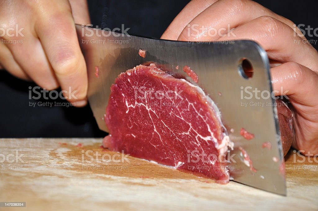 Skilled Chef cuts schnitzel from a peace of meat meat. royalty-free stock photo