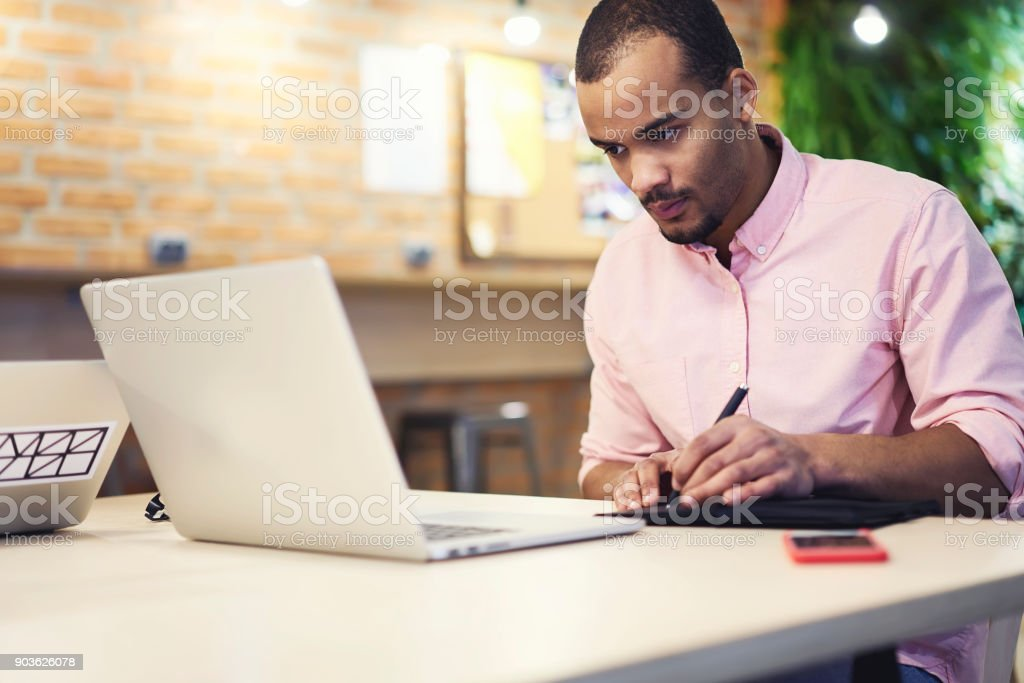 Skilled concentrated afro american graphic designer drawing sketch of creative planning in notebook while watching online scheme of office building on modern laptop computer sitting in office stock photo