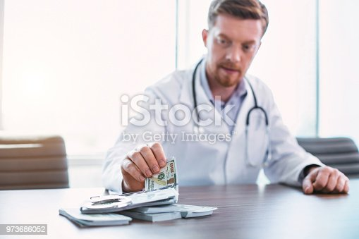 182362845 istock photo Skilled doctor taking bribes in his office 973686052