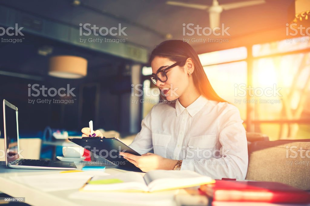 Skilled experienced female owner of restaurant making checklist of duties for stuff  to increase income developing successful strategy for business while sitting at table using laptop computer stock photo