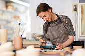 Content attractive skilled young lady in apron standing at table and drawing blue leaves on ceramic bowl in pottery workshop