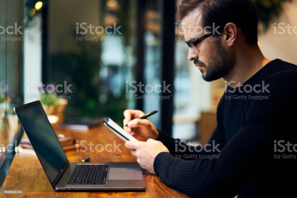 Skilled male administrative manager noting contacts of media...