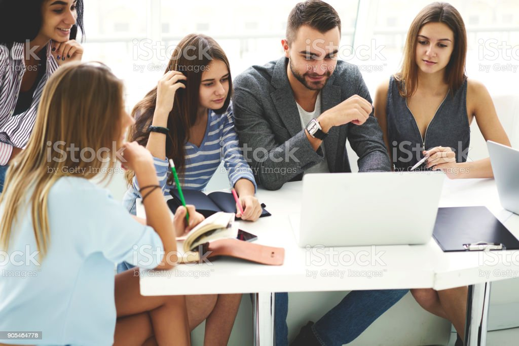 Skilled male business coach checking projects of his student presenting best ones to female pupils speaking about advantages and disadvantages of work during lesson in university using laptop stock photo