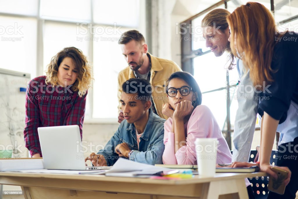 Skilled male IT developer presenting to colleagues his new application for digital devices consulting about advantages in use, diversity group of coworkers watching promotional video on laptop stock photo