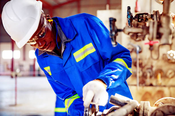 Skilled Pump Room Operator Closing the Pressure Valve at a Factory in Africa stock photo