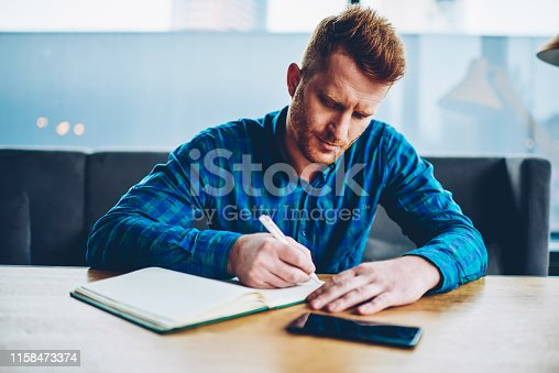 1174436608 istock photo Skilled red haired student writing down homework in copybook studying at wooden table in coworking space.Pensive young man dressed in casual shirt noting checklist in notepad during free time 1158473374
