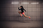 One woman, young and fit woman, training outdoors at night alone, long jump training.
