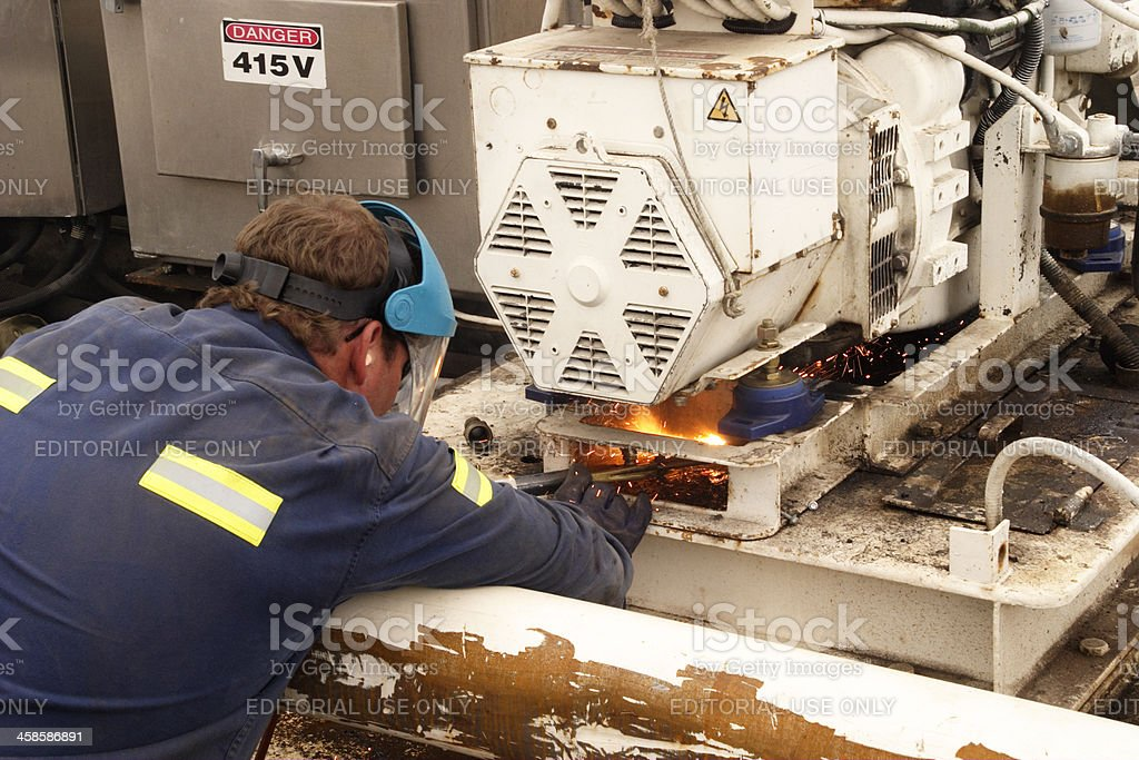 Skilled worker repairing machinery with oxy equipment stock photo