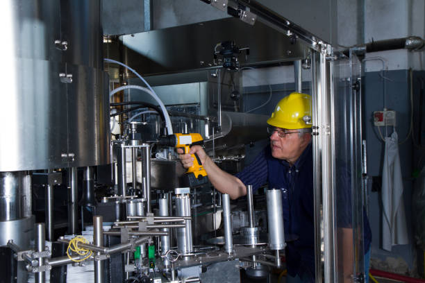 skilled worker while fixing a bottling plant during maintenance work stock photo