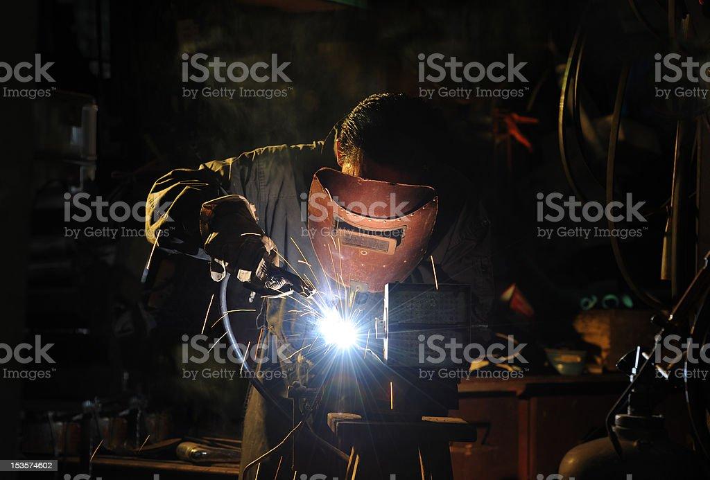 skilled factory welder working in a workshop with dark surrounding