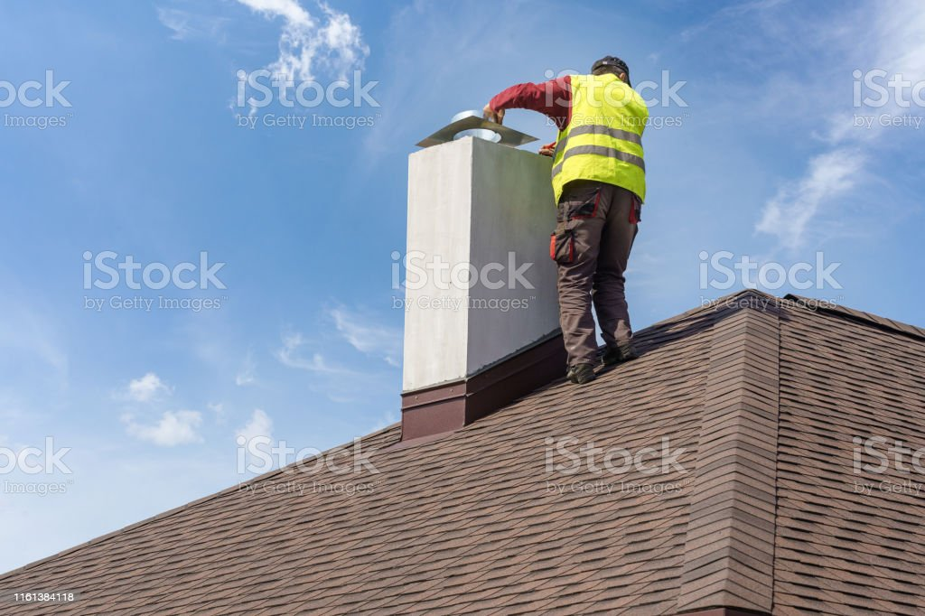 Skilled workman in protective work wear and special uniform install...
