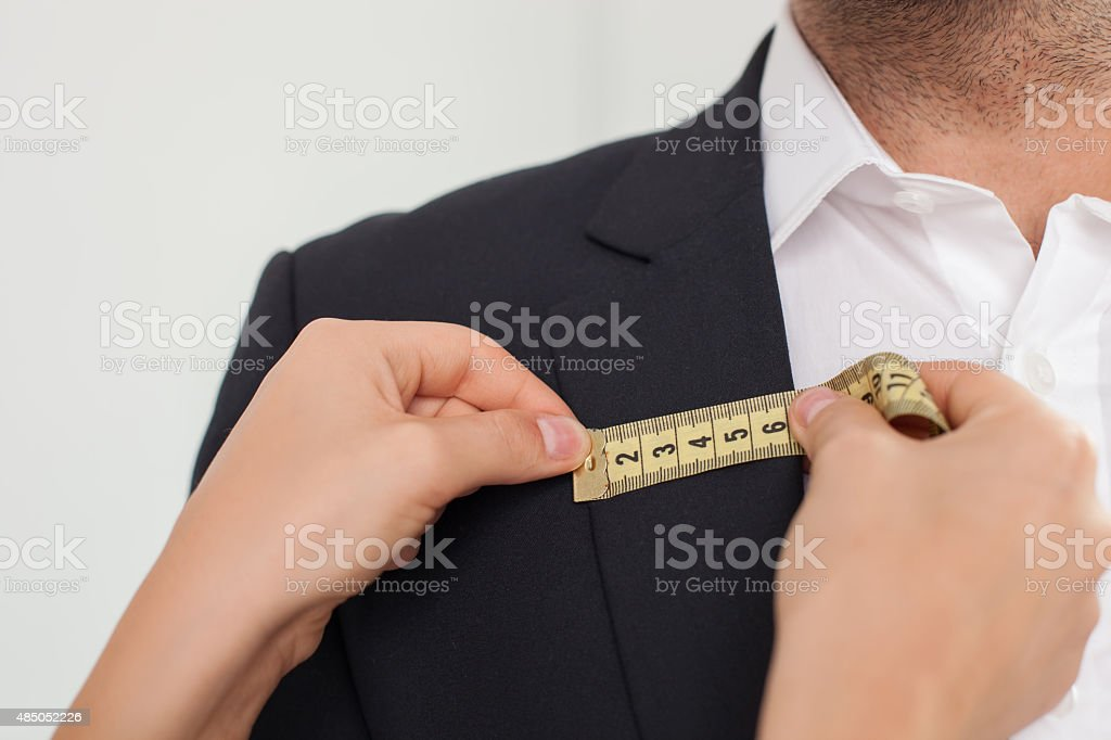 Skilled young female tailor is working with her customer stock photo