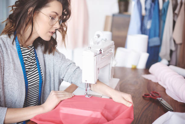 skilled young tailor sewing on machine - seam stock photos and pictures