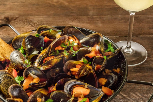 sartén de marinara mejillones con vino blanco en fondo rústico - comida francesa fotografías e imágenes de stock