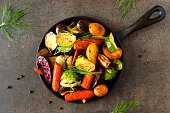 Cast iron skillet of roasted autumn vegetables, above view over a dark stone background
