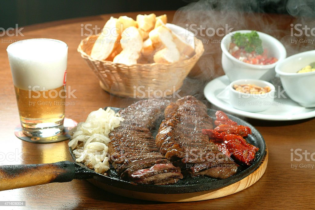 Skillet of sizzling barbecue meat with chips and beer stock photo