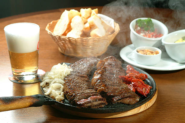 skillet of sizzling barbecue meat with chips and beer - 食用份量 個照片及圖片檔