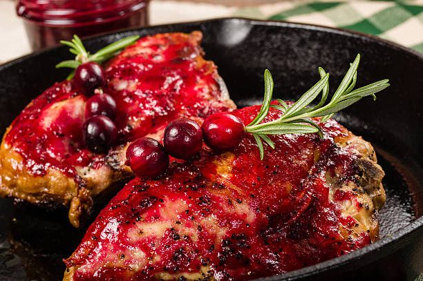 Skillet with two glazed chicken breasts stock photo