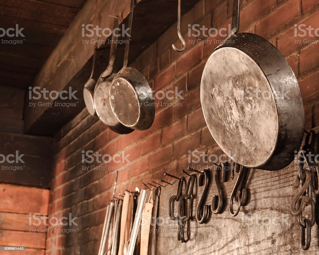 Skillets Hanging in Colonial Kitchen stock photo