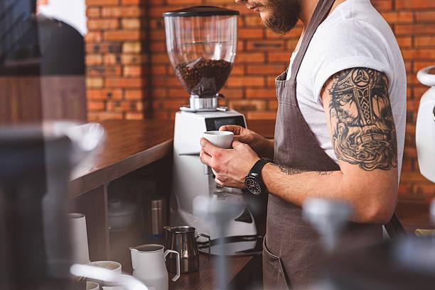 skillful bartender brewing coffee in cafeteria - kaffeetasse tattoo stock-fotos und bilder