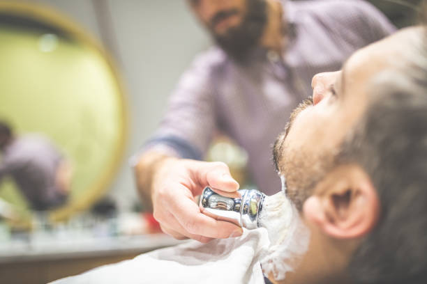 Skillful beautician preparing to shave stubble. Professional barber applying shaving foam on client skin in barbershop. shaving brush shaving cream razor old fashioned stock pictures, royalty-free photos & images
