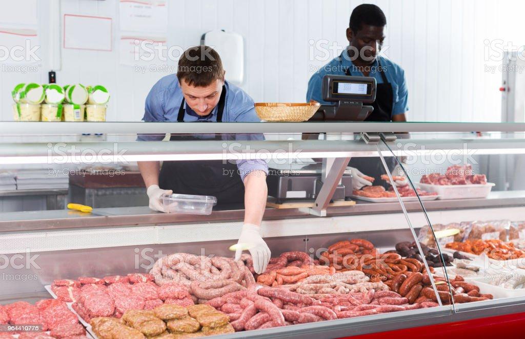 Behendig slager met collega werken achter balie - Royalty-free Assistent Stockfoto