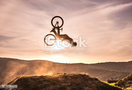 Mountain bike rider exercising at sunset and performing backflip against the sky. Copy space.