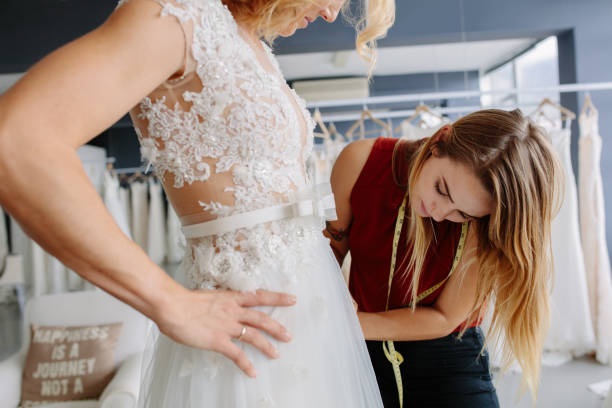 Skillful designer fitting bridal gown to bride stock photo