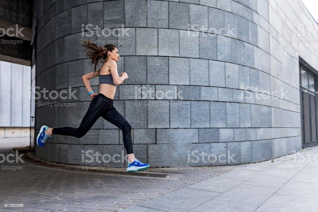 Skillful female athlete jogging outdoors stock photo