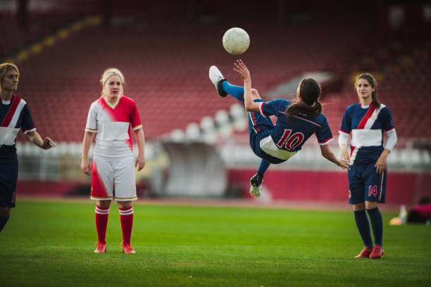 Skillful female soccer striker doing bicycle kick during the game. stock photo