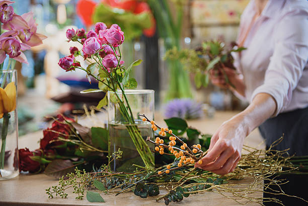 Skillful florist making bouquet in workshop Close up of female hand is taking branch of rowan to join bunch of flowers. Focus on roses and other plants on table in flower shop flower arrangement stock pictures, royalty-free photos & images