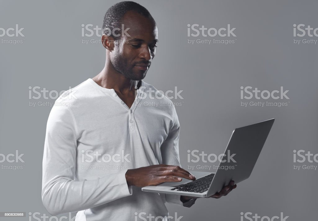 Skillful guy is typing on notebook stock photo