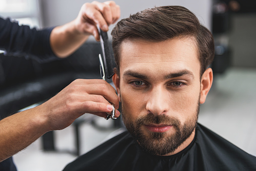 986804130 istock photo Skillful hairdresser cutting male hair 640272644