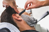 istock Skillful hairdresser shaving beard by blade 640276268