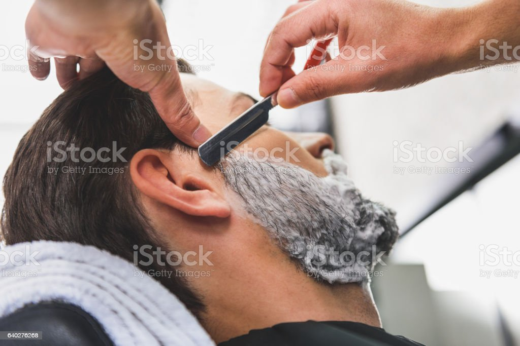 Skillful hairdresser shaving beard by blade stock photo