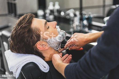 istock Skillful hairdresser using blade for shaving beard 640276472