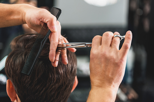 986804130 istock photo Skillful male barber doing haircut 640273790