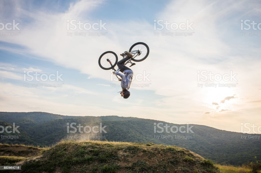 Skillful man on bicycle performing backflip in nature. stock photo