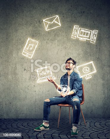 istock skillful man sitting on chair and juggling with electronic devices icons 1064699680
