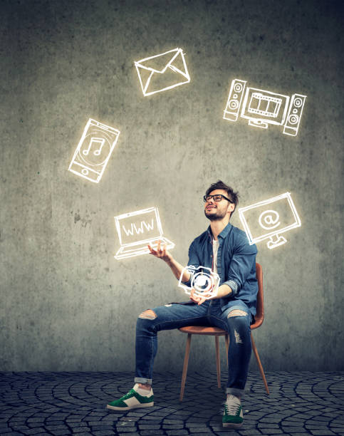 skillful man sitting on chair and juggling with electronic devices icons stock photo