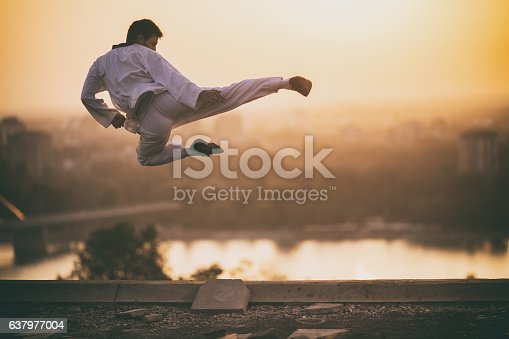 Black belt karate fighter exercising at sunset and doing jump kick while being in mid air.