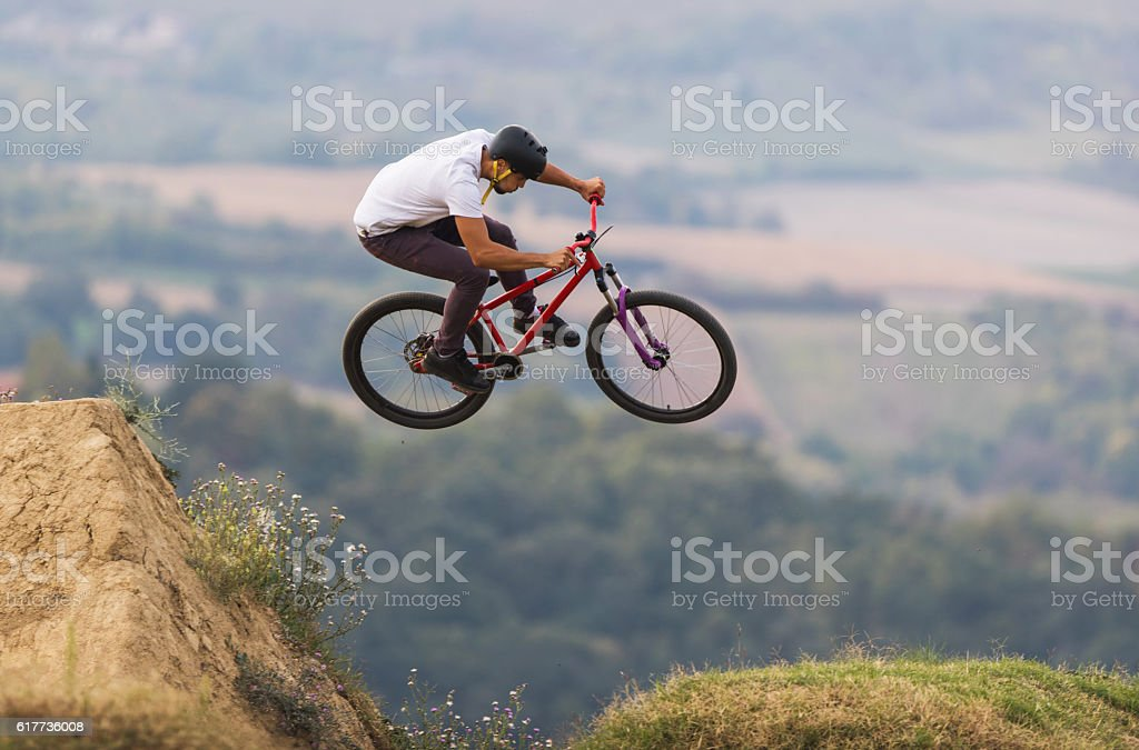 Skillful mountain bike rider jumping over dirt hills. stock photo