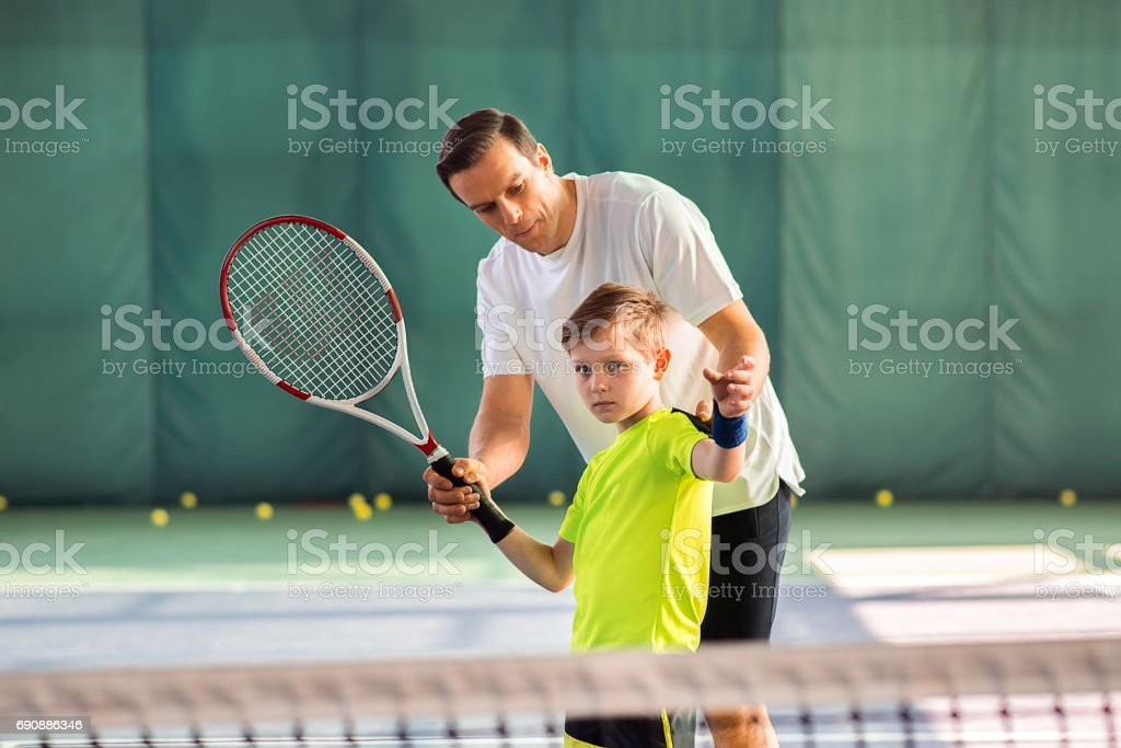 Skillful trainer teaching kid holding racquet stock photo