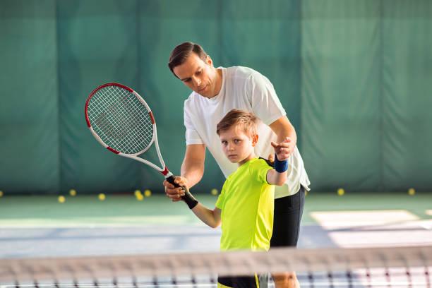Skillful trainer teaching kid holding racquet stock photo