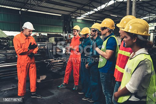 istock Skillful worker attending brief meeting in the factory . 1302718747